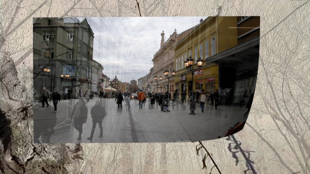 image of Novi Sad superimposed with Toronto city scene arranged as a photograph blowing along the backdrop wall and woods from of On the Margin of History.