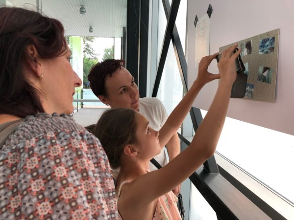 family interacting with AR installation On the Margin of History as part of Still/ed Here exhibition in Novi Sad